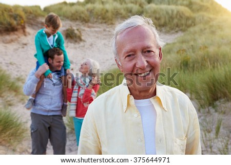 Extended Family Group Walking By Sand Dunes - stock photo