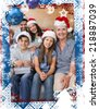 Extended family in Christmas hats with gift boxes in living room against christmas themed frame - stock photo