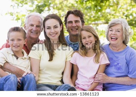 Extended family outdoors smiling - stock photo