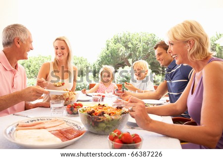 Extended family, parents, grandparents and children, eating outdoors - stock photo