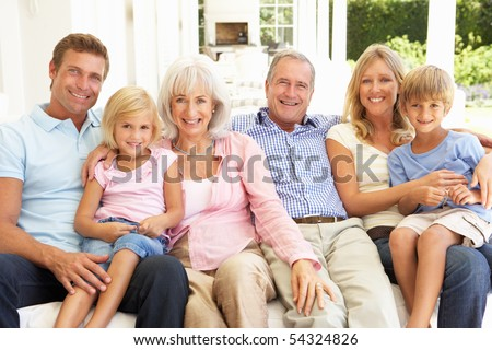 Extended Family Relaxing Together On Sofa - stock photo