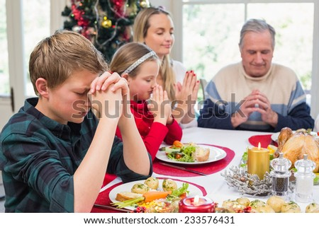 Extended family saying grace before christmas dinner at home in the dining room - stock photo