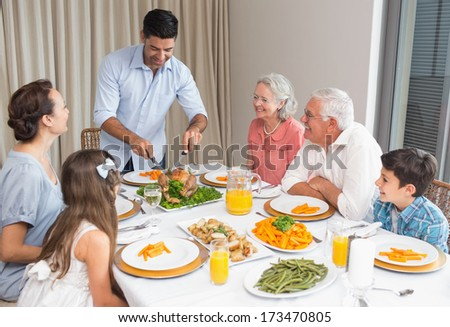 Extended family sitting at dining table in the house