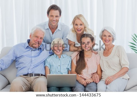 Extended family sitting on couch and using a laptop - stock photo