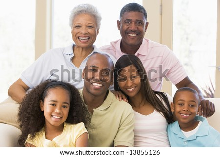 Extended family sitting on sofa - stock photo