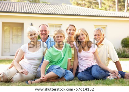 Extended Family Sitting Outside Dream Home - stock photo
