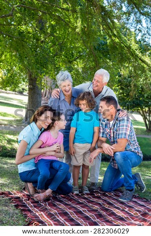 Extended family smiling in the park on a sunny day - stock photo