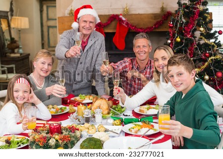 Extended family toasting at christmas dinner at home in the living room - stock photo