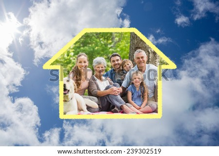 Extended family with their pet dog sitting at park against bright blue sky with clouds