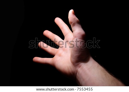 Extended hand for help on a black background - stock photo