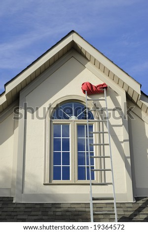 Extension ladder resting on side of second floor window of stucco house with red rag rolled on last step against blue skies