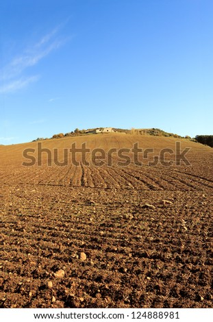 Extensive crop field, plowed land and house on the hill