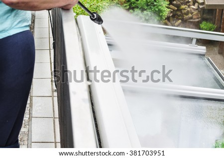 Exterior cleaning and building cleaning a glass roof with high pressure water jet. - stock photo