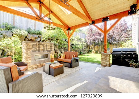 Exterior covered patio with fireplace and furniture. Wood ceiling with skylights. - stock photo
