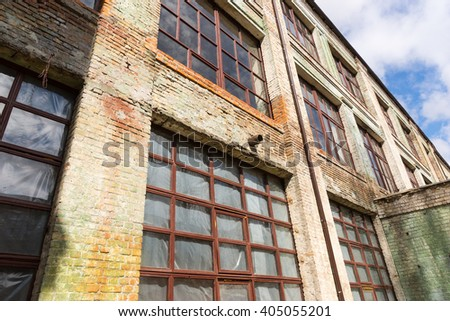 Exterior facade of a grungy old commercial building with large windows and stained brickwork viewed from below - stock photo