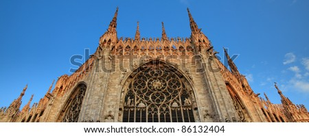 Exterior facade of Milan cathedral, the dome, duomo, illuminated by the first sunrays in early morning, Lombardy, Italy - stock photo