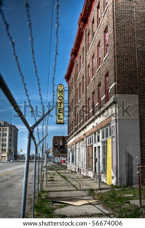 Exterior image of an abandoned hotel with barbed wire fence in the foreground. - stock photo