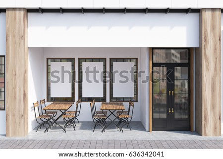 exterior of a cafe with white walls three posters hanging on them and wooden tables