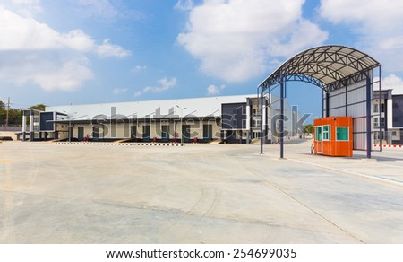 exterior of a commercial warehouse with a scale weigh station before and after load - stock photo