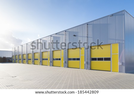 exterior of a commercial warehouse with yellow roller doors - stock photo