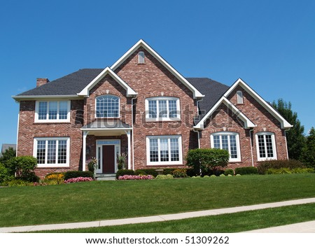 Exterior of a large two story brick residential home containing plenty of copy space, - stock photo