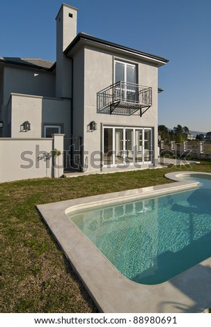 Exterior of a luxury house with a swimming pool on a sunny day - stock photo