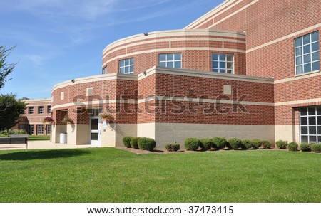 exterior of a modern brick high school by a lush green lawn - stock photo