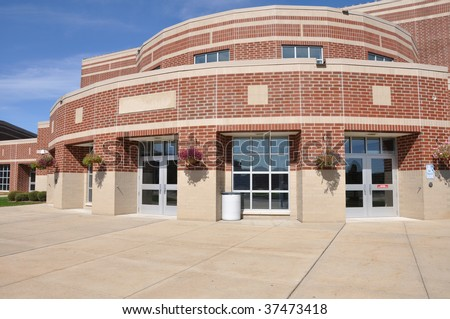 exterior of a modern red brick building by a concrete sidewalk - stock photo