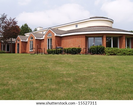 exterior of a modern round brick building with many windows - stock photo