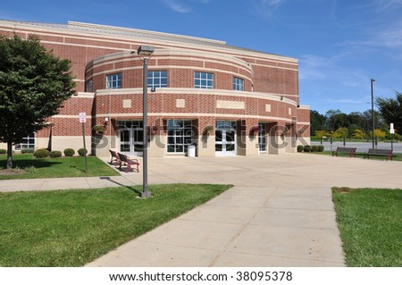 exterior of a modern rounded red brick school building by a concrete sidewalk - stock photo