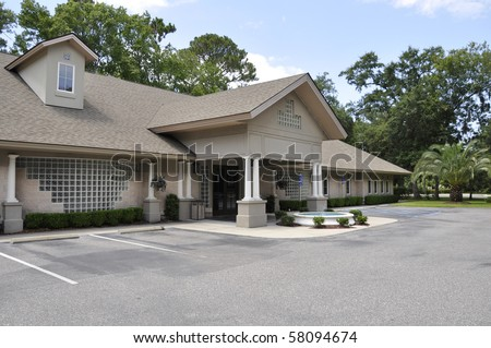 Exterior of a small medical office building by a macadam parking area. - stock photo