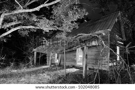 exterior of an old abandoned house at night - stock photo