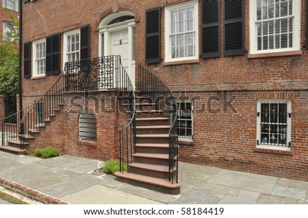 Exterior of an old red brick home with a double staircase.  The home is in Savannah, Georgia. - stock photo