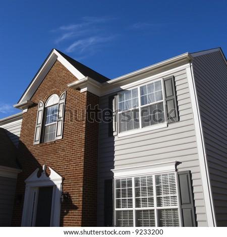 Exterior of brick and vinyl siding house. - stock photo