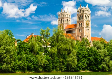 Exterior of church in city of Munich with trees, blue sky and cloudscape background; Germany. - stock photo