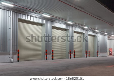 Exterior of factory with shutter door, night time. - stock photo