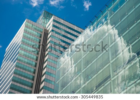 Exterior of glass office building and blue sky - stock photo