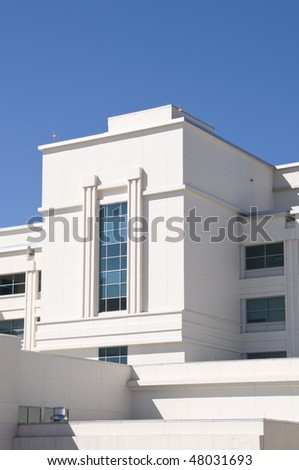 Exterior of hospital with tinted windows and blue sky - stock photo