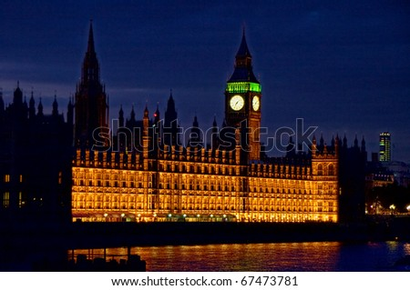 Exterior of Palace of Westminster with Big Ben clock tower illuminated at night over Thames river, London, England - stock photo