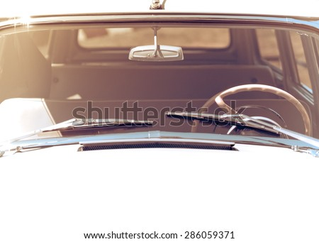 Exterior of the old automobile with windshield wipers, steering wheel and front window. Retro car in vintage toned effect with copy-space for text. Oldtimer automobile, front view. - stock photo