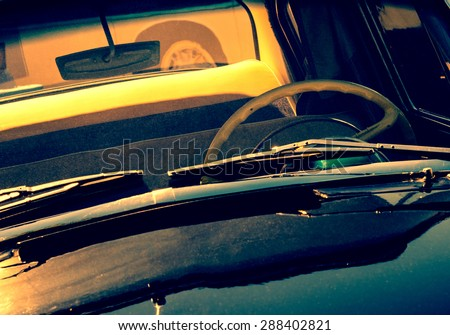 Exterior of the retro black automobile with windshield wipers, steering wheel and front window. Old car in vintage toned effect at sunset light. Oldtimer automobile, front view. - stock photo