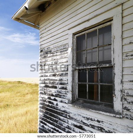 Exterior of weathered abandoned building with peeling paint and window in grassland. - stock photo