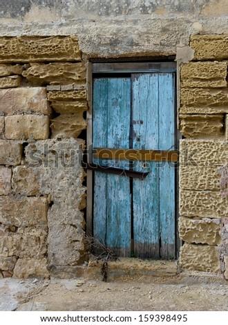 Exterior,Old door fragment, old door texture view, abstract scene, nobody at home, weathered door, close door in bright wall background, colourful door, old object, destruction  - stock photo
