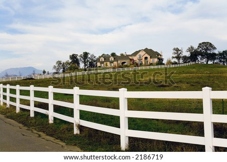 Exterior shot of a large luxurious home on acreage set up for horses. - stock photo