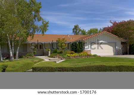 Exterior shot of a ranch style home that is wonderfully landscaped and has a tile roof. - stock photo