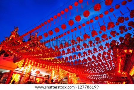 Exterior shot of a temple with a fisheye view of red lanterns against blue skies taken at sunset. - stock photo