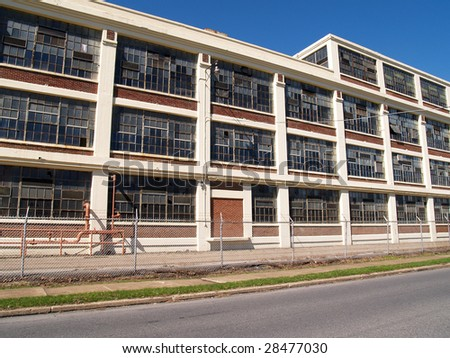 exterior view of a large old abandoned factory - stock photo
