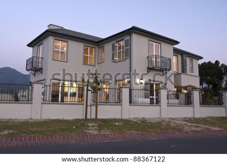Exterior view of a modern house at dusk - stock photo
