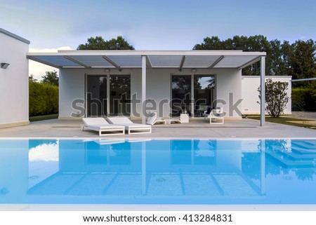 exterior view of a villa in foreground the swimming pool - stock photo