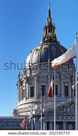 Exterior view of San Francisco City Hall dome with flags - stock photo